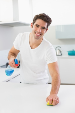 clean kitchen: Portrait of a smiling young man cleaning kitchen counter in the house Stock Photo