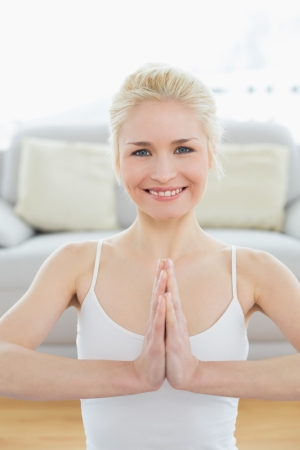 Portrait of a toned young woman sitting in Namaste position at fitness studio Stock Photo