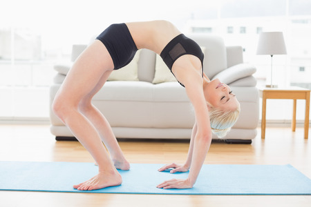 Full length side view of a fit young woman doing the wheel pose in fitness studio photo