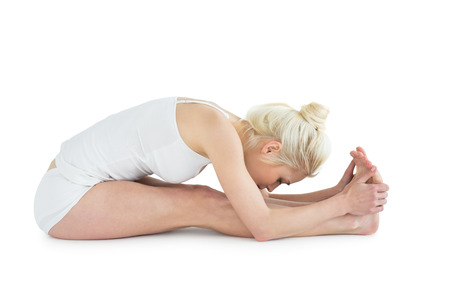 Full length side view of a toned young woman doing the paschimottanasana pose over white background photo