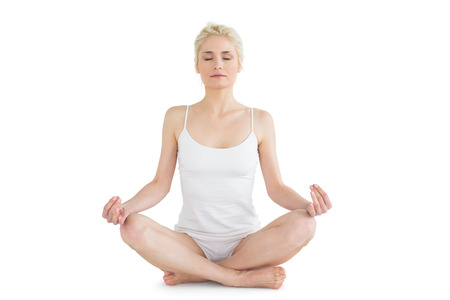 Full length of a toned young woman sitting in lotus pose with eyes closed against white background photo
