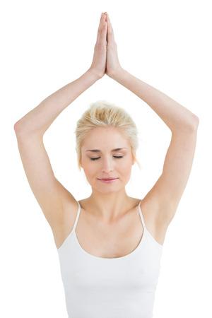 joined hands: Mujer joven entonada con las manos juntas sobre la cabeza y los ojos cerrados contra el fondo blanco