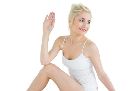 ardha: Toned young woman in the Ardha Matsyendrasana position against white background