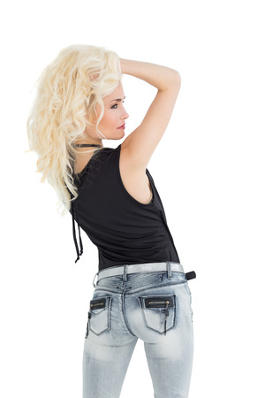 Rear view of a beautiful casual blond posing over white background photo