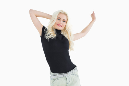 Beautiful casual young blond dancing over white background photo