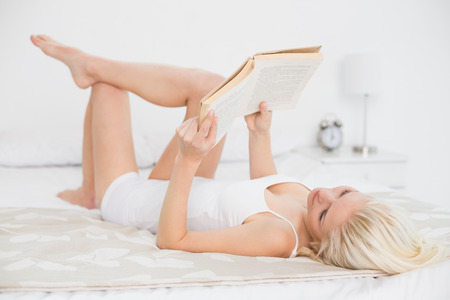 fair woman: Full length of a relaxed young woman reading a book in bed at home