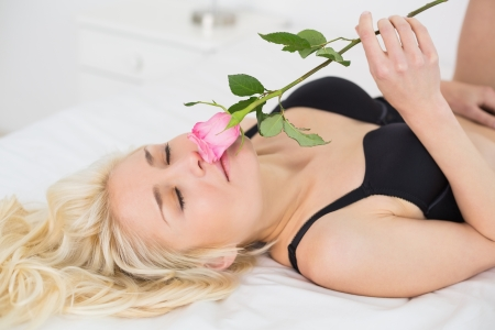Close up of a beautiful young woman lying in black lingerie with rose on bed photo