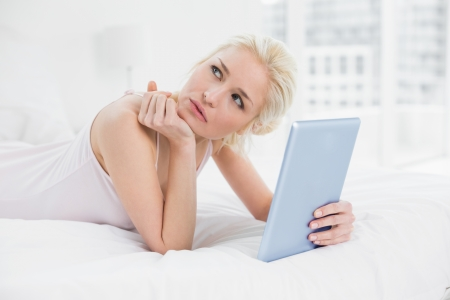 Thoughtful casual young blond with tablet PC lying in bed at home photo