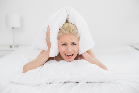 Portrait of an angry young woman covering ears with pillow in bed at home photo