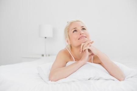 joined hands: Relajado mujer muy joven con las manos juntas en la cama en su casa