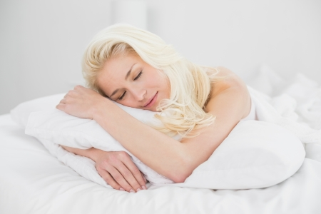 Close up of a pretty young woman sleeping in bed at home photo