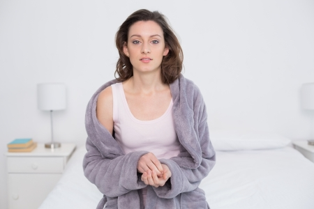 Portrait of a beautiful young woman in bathrobe sitting in bed at home photo