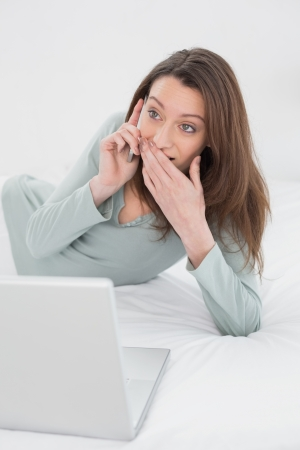 Shocked casual young woman using cellphone and laptop in bed at home photo