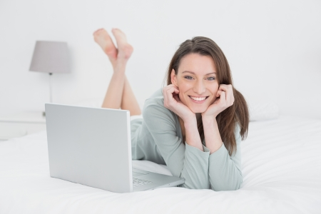 Portrait of a relaxed casual young woman with laptop lying in bed at home photo