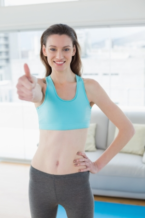 Portrait of a smiling toned young woman gesturing thumbs up in fitness studio photo