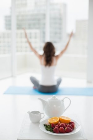 Blurred toned young woman sitting in meditation posture with healthy food in foreground at fitness studio photo