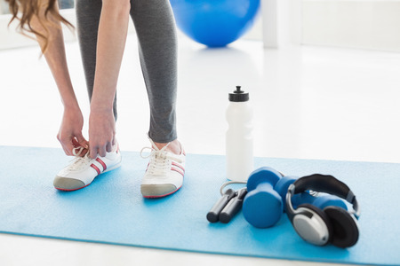 Low section of a woman tying shoes with sporty equipment on floor in fitness center photo