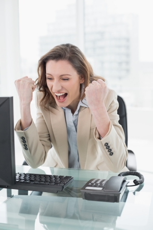 Elegant businesswoman cheering with clenched fists at office desk photo