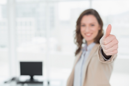 Portrait of an elegant smiling businesswoman gesturing thumbs up in a bright office photo