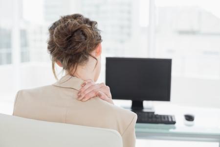 밝은 사무실에서 컴퓨터 앞에 목에 통증이있는 사업가의 후면보기 스톡 콘텐츠