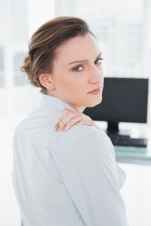 Rear view portrait of a businesswoman with neck pain in front of computer in a bright office photo