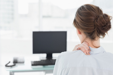 Rear view of a businesswoman with neck pain in front of computer in a bright office