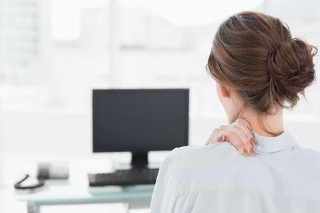 밝은 사무실에서 컴퓨터 앞에 목에 통증이 사업가의 후면보기