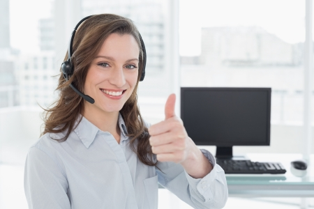 Businesswoman wearing headset while gesturing thumbs up in front of computer in a bright office photo