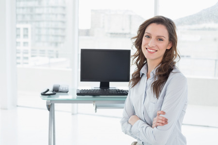 Portrait of a smiling businesswoman in front of computer in a bright office photo