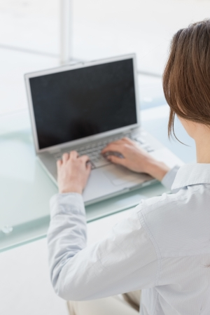 Close up rear view of a brown haired businesswoman using laptop in a bright office photo