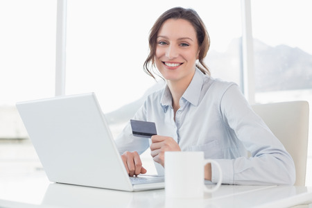Portrait of a smiling businesswoman doing online shopping through laptop and credit card in office photo