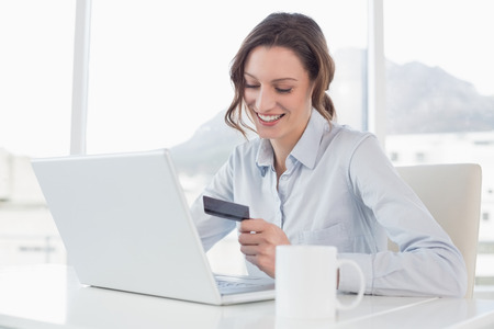 tied down: Smiling businesswoman doing online shopping through laptop and credit card in office