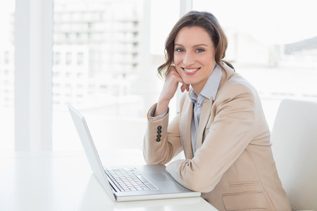 Portrait of a smiling young businesswoman with laptop in a bright office photo