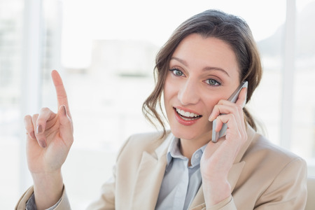Close up of a smiling elegant businesswoman using mobile phone in a bright office photo
