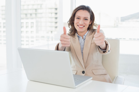 Portrait of an elegant smiling businesswoman gesturing thumbs up with laptop in a bright office photo