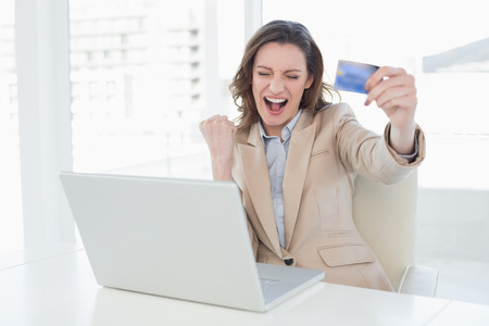 Excited businesswoman doing online shopping through laptop and credit card in office photo