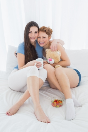 Full length portrait of cheerful young female friends with coffee cups in bed at home photo