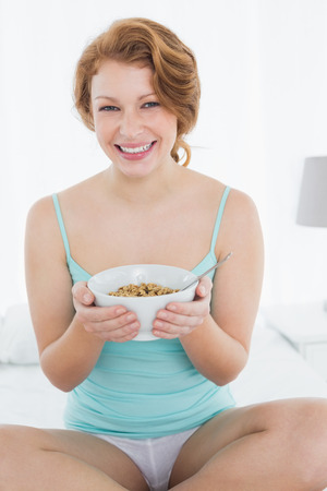 Portrait of a smiling young female with a bowl of cereal sitting on bed at home photo