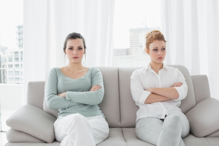 Unhappy young female friends not talking after argument at home on the couch Foto de archivo