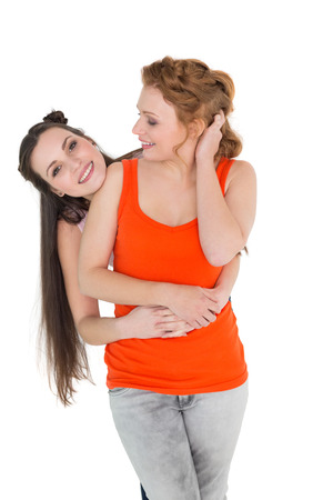 Cheerful young female embracing her friend from behind over white background photo