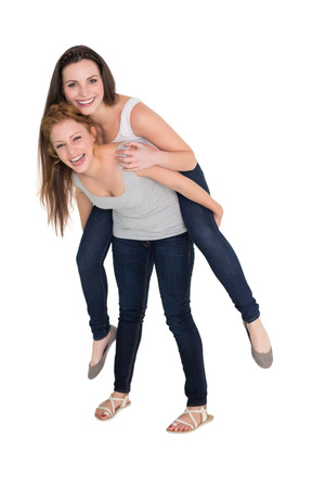 Full length portrait of a young female piggybacking friend over white background photo