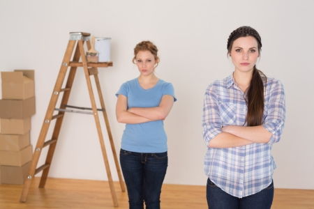 Portrait of two female friends standing with arms crossed in a new house photo