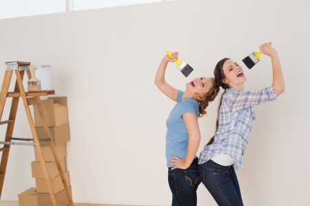 Two cheerful female friends singing into paintbrushes by ladder in a new house photo