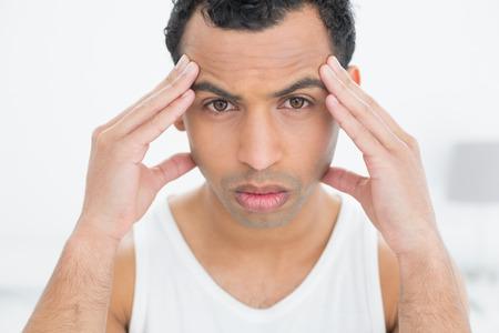 ojos marrones: Close-up retrato de un hombre joven que sufre de dolor de cabeza en la cama en su casa