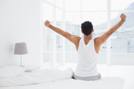 bed sheet: Rear view of a young man waking up in bed and stretching his arms Stock Photo