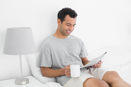 Relaxed young man reading newspaper while holding coffee cup in bed at house photo