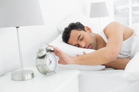 extending: Sleepy young man in bed extending hand to alarm clock Stock Photo