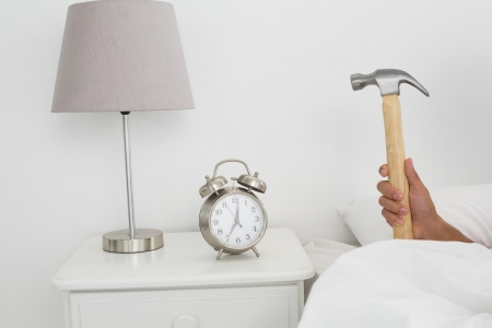 Close-up of a mans hand smashing alarm clock with hammer in bed at home photo