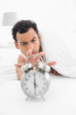 extending: Close-up of a sleepy young man in bed extending hand to alarm clock at home Stock Photo