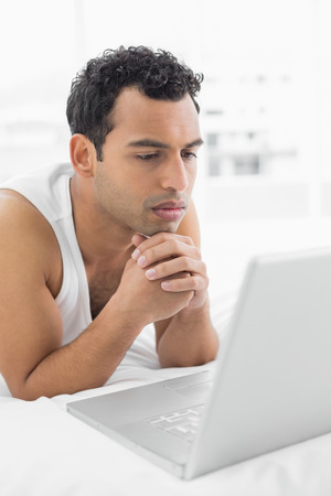 Casual young man using laptop in bed at home photo